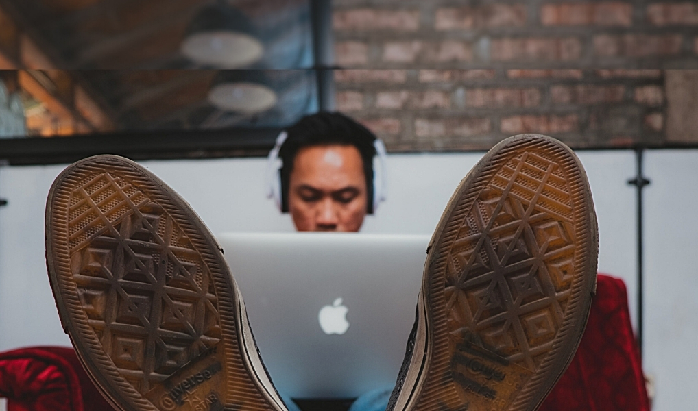 Man works with laptop on his legs.