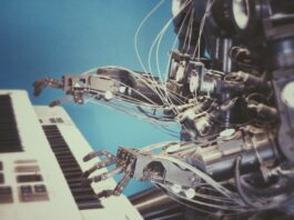 Robot plays on a musical keyboard.