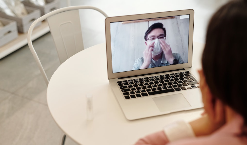 Laptop monitor showing man wearing mask