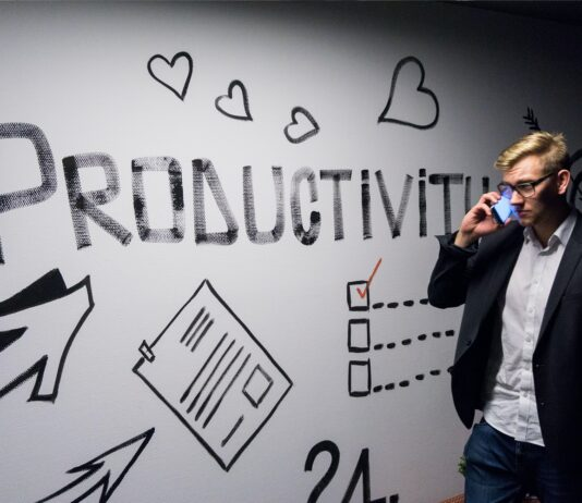 Man standing next to productivity drawing
