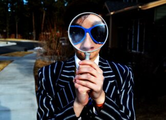 Woman wearing sunglasses looking through a magnifying glass